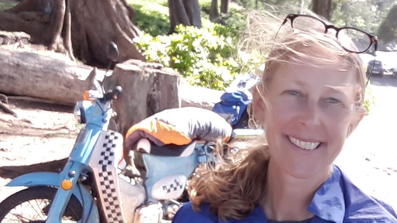 Sasha Nealand in the field, dirt bike in background.