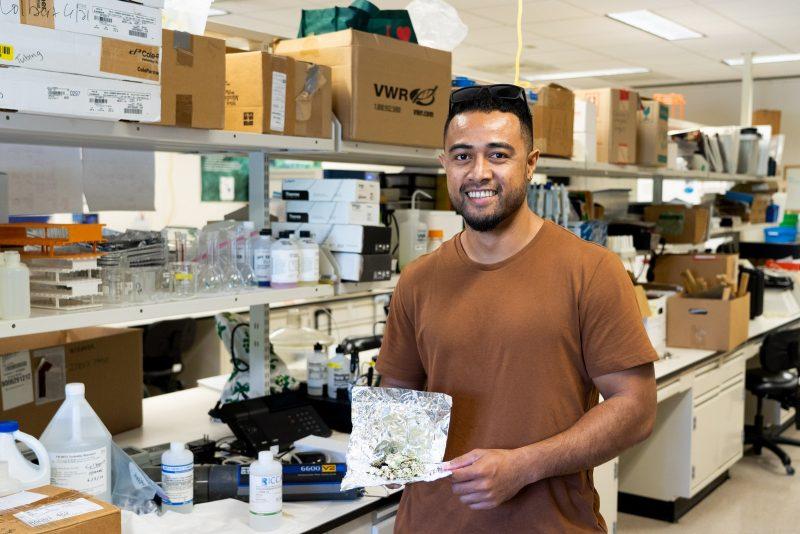 Bryan Tonga holds seaweed sample in lab.
