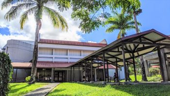 Red-roofed UH Hilo College of Business and Economics, covered walkway into the entrance.