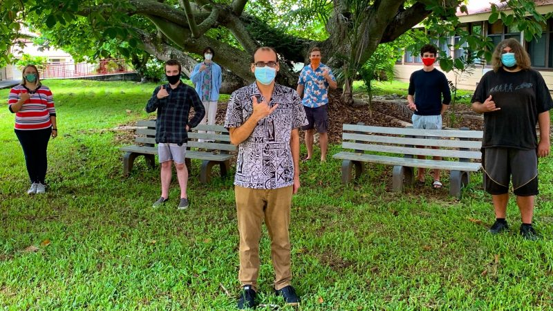 Group of students and professor stand under a large tree, everyone is wearing masks and six feet apart.