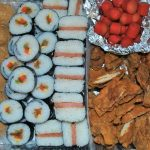 Tray of sushi, musubi, fried chicken and prawns.
