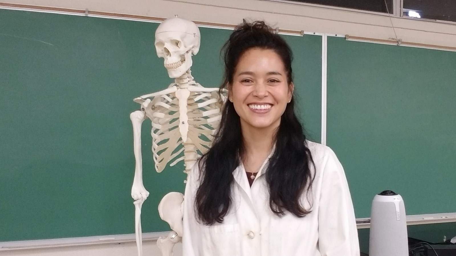 Jenni Guillen in classroom with skeleton over her right shoulder, blackboard in distance.