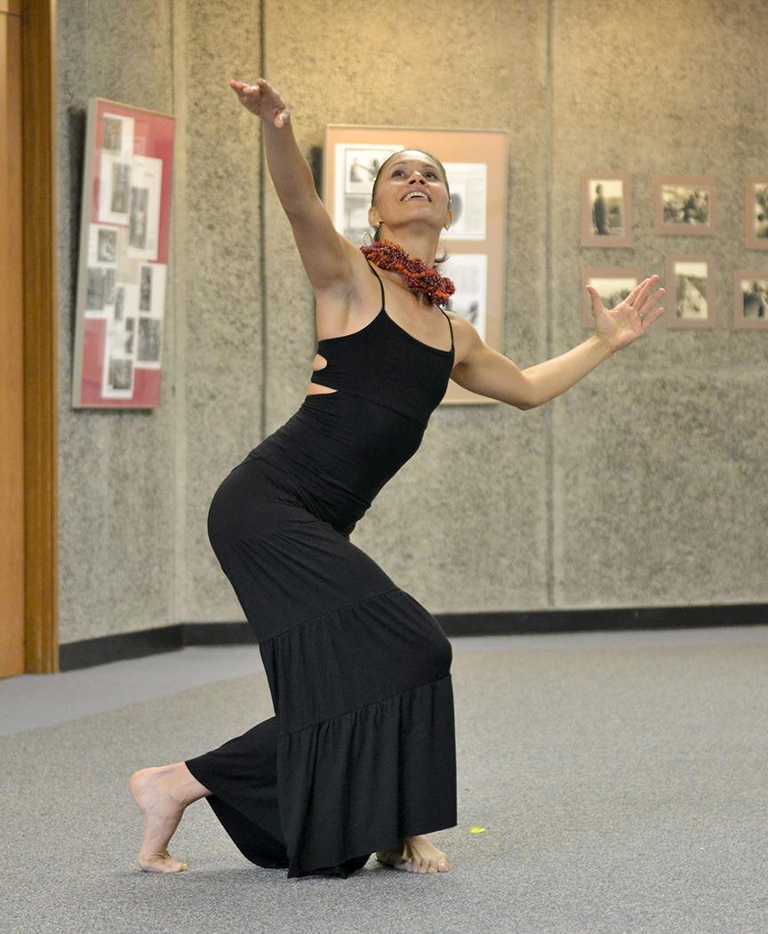 Hula dancer in long black dress.