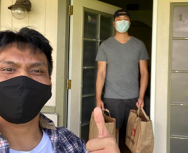Man holds two bags of groceries just delivered to him.