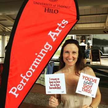 """Justine Mattos stands next to a banner reading UH Hilo Performing Arts. She holds two small signs, one in Hawaiian, and one translation """"YOU'VE TOTALLY GOT THIS!"""""""