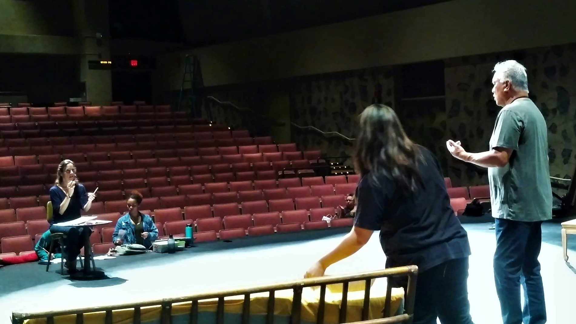 A left is director Justina Mattos giving two actors direction on the stage. Background is empty tiered theatre seating.