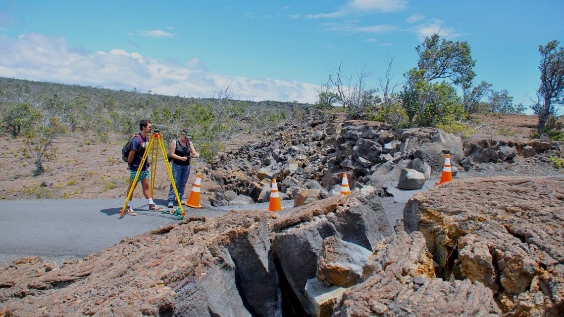 Two students in lava field with measuring instruments.