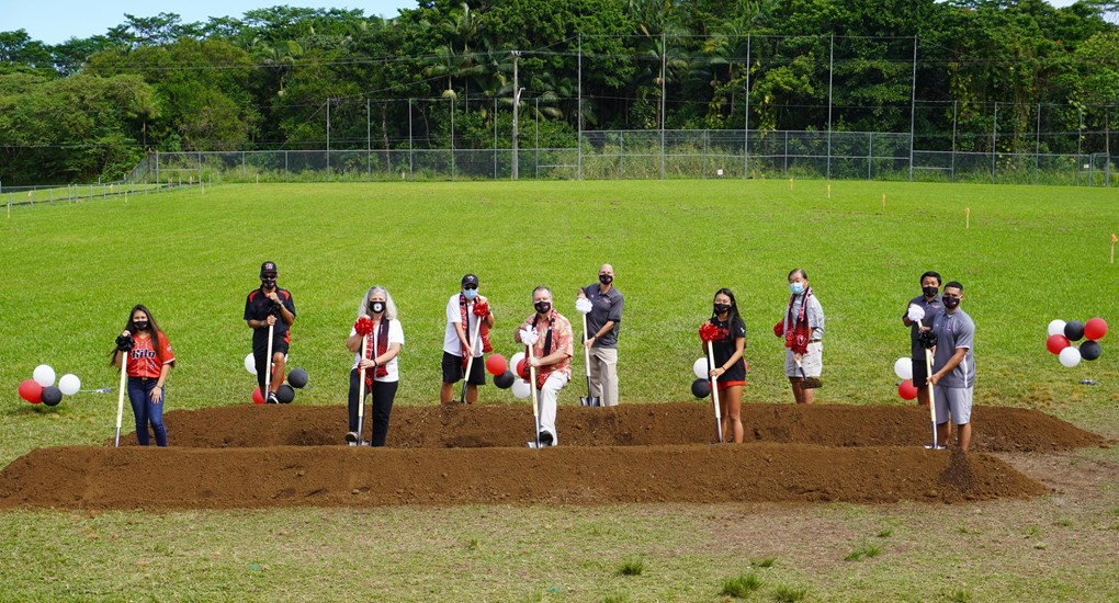Two lines of dignitaries with shovels in open field.