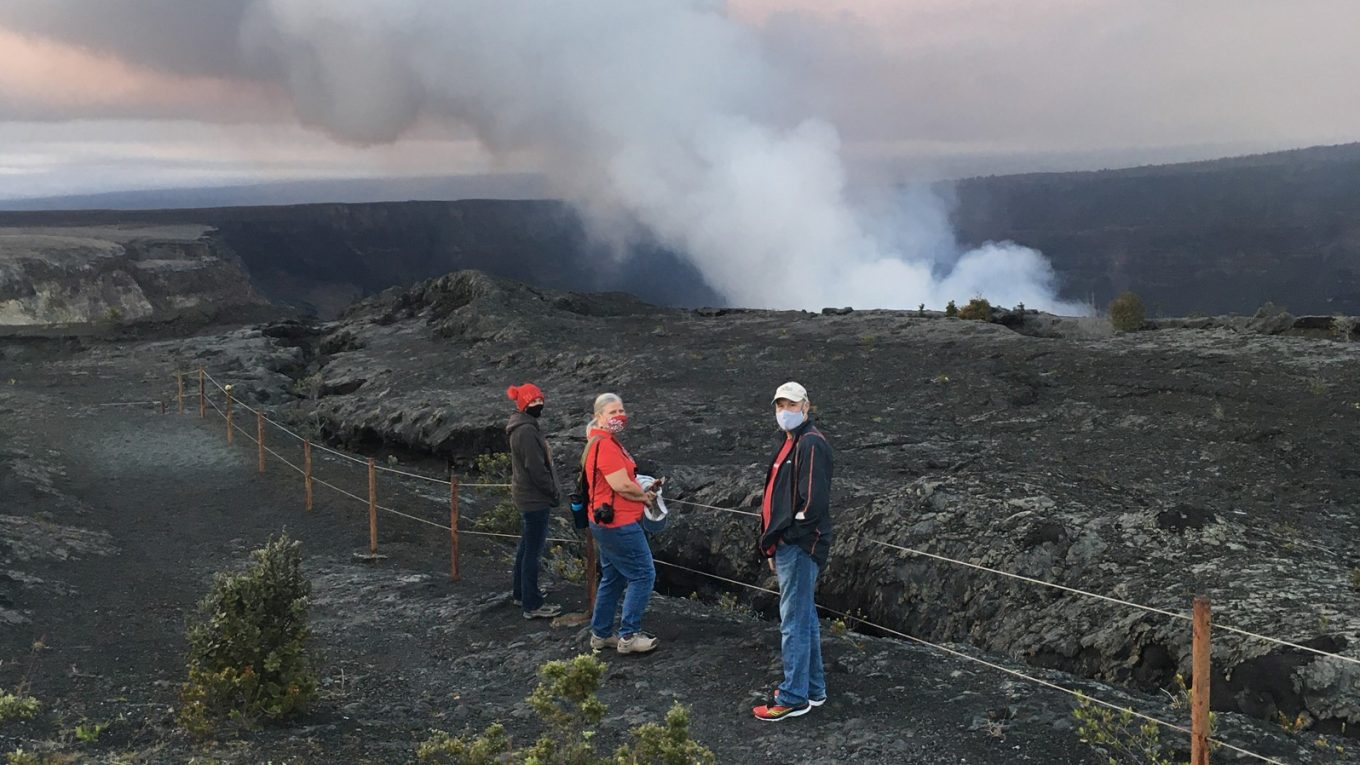 Three people at overlook of volcanic eruption and plume coming out of caldera.