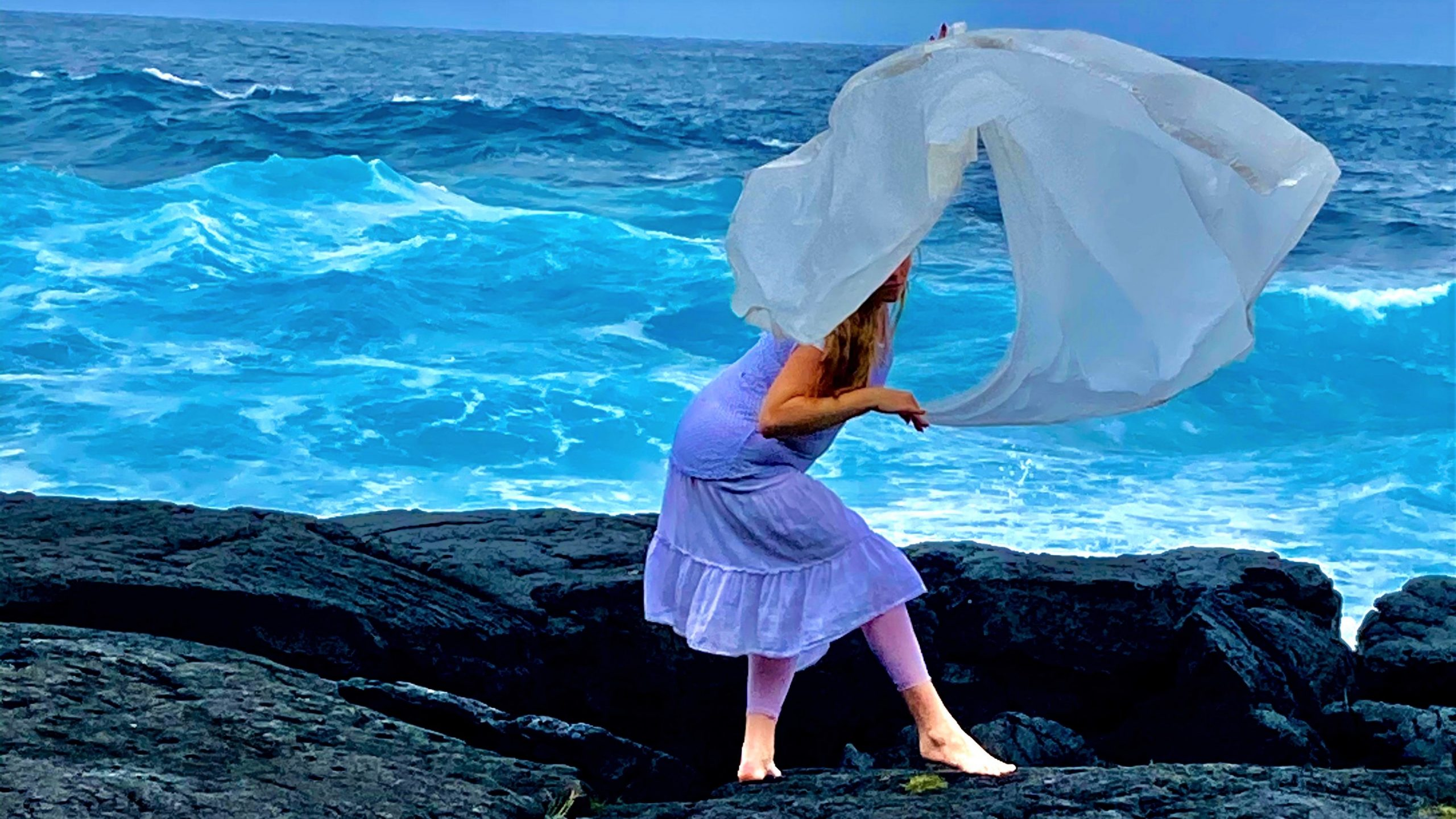 Woman on lava sea cliff with billowing white scarf that looks like a wave.