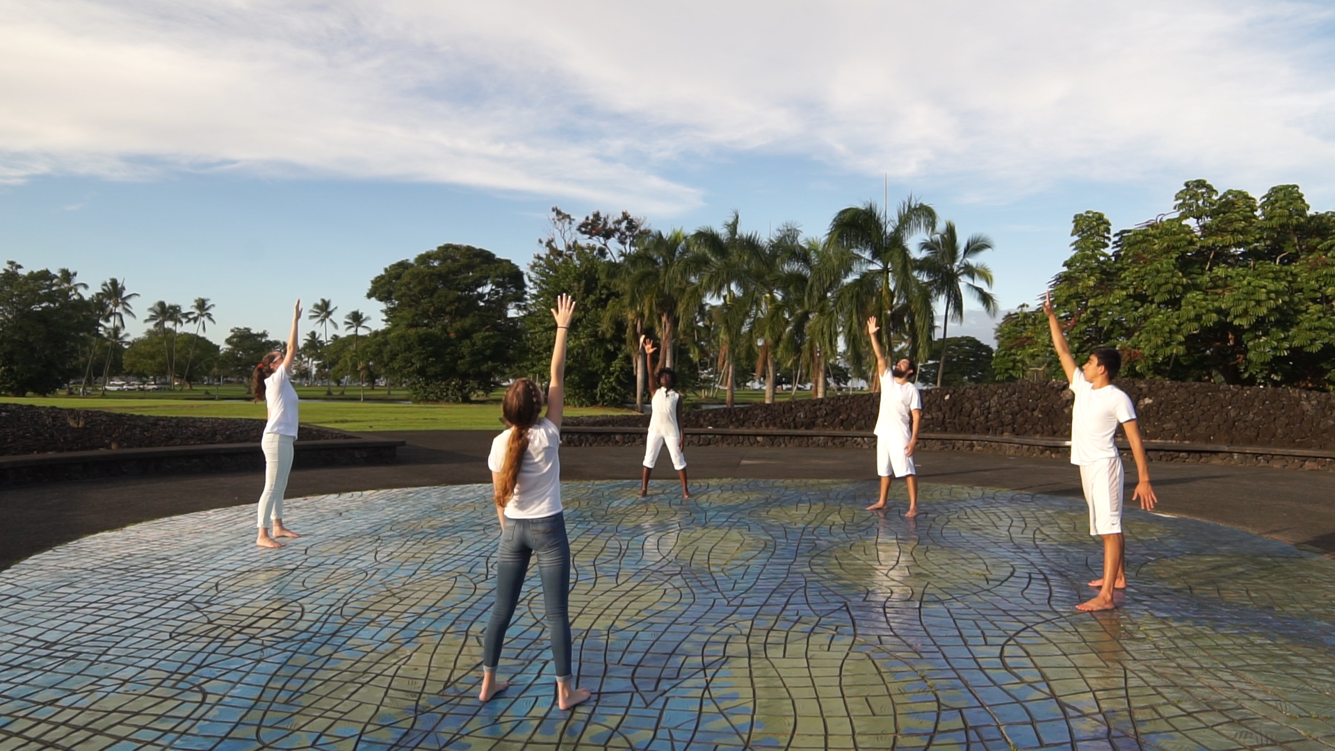 Five dancers stand on a circular floor mosaic, each with one arm extended him above their heads.