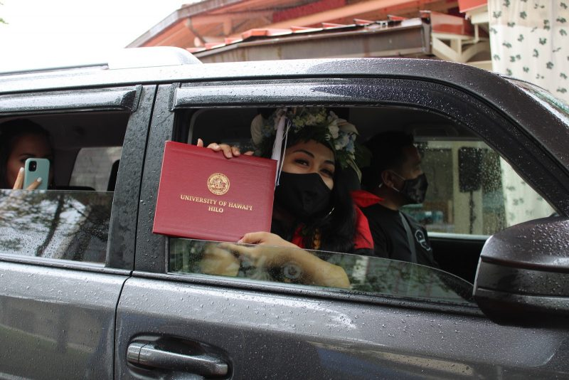 Graduate in car, with lei and mask, holds up red diploma cover.