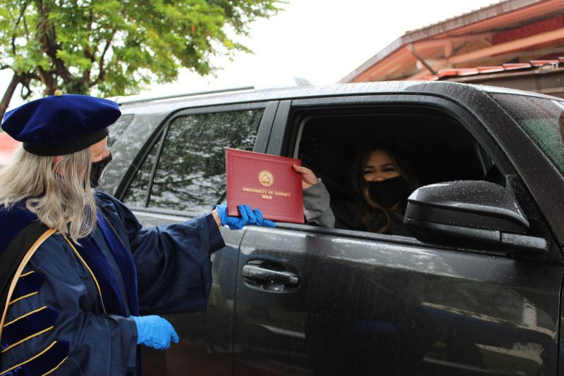 Chancellor, in blue PPE gloves, hands graduate red diploma cover through car window.