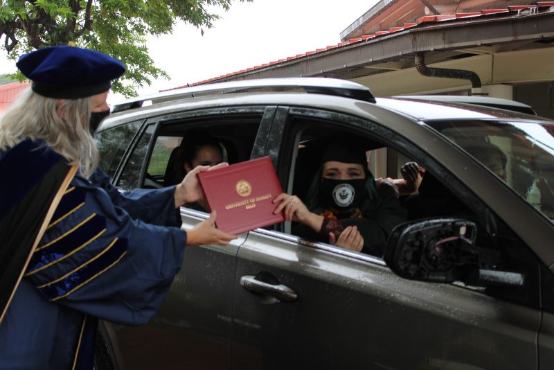 An emotional graduate in car reaches out through window to take red diploma cover from the Chancellor.