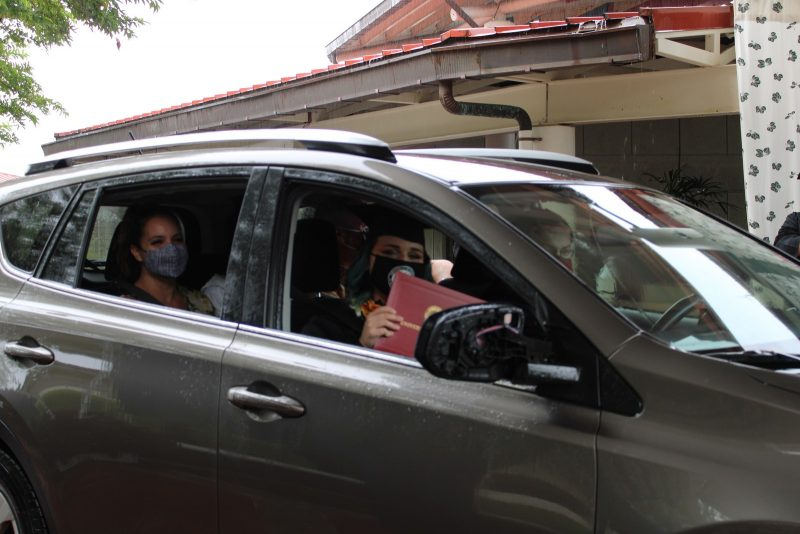 A graduate drives by with red diploma cover in hand.