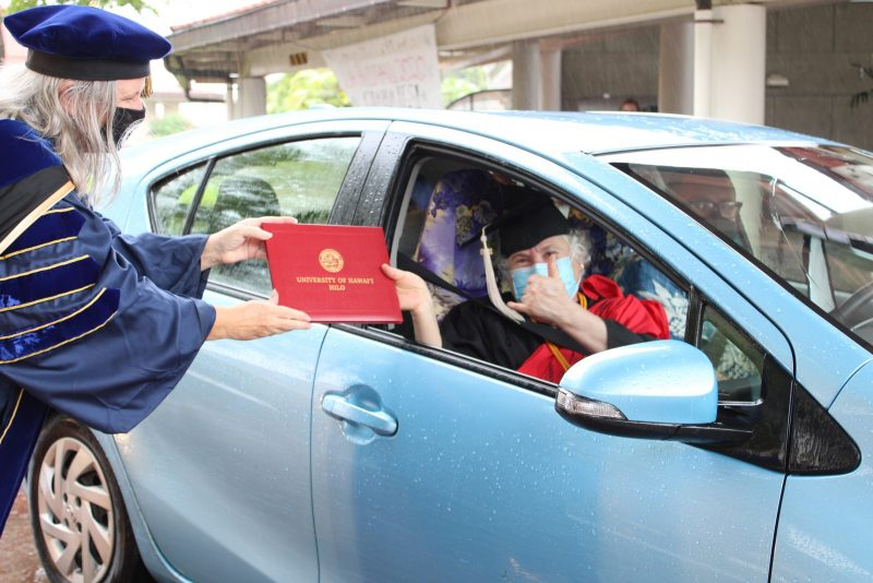 An older woman graduate in the passenger side of a blue car reaches out to take red diploma cover from the Chancellor.