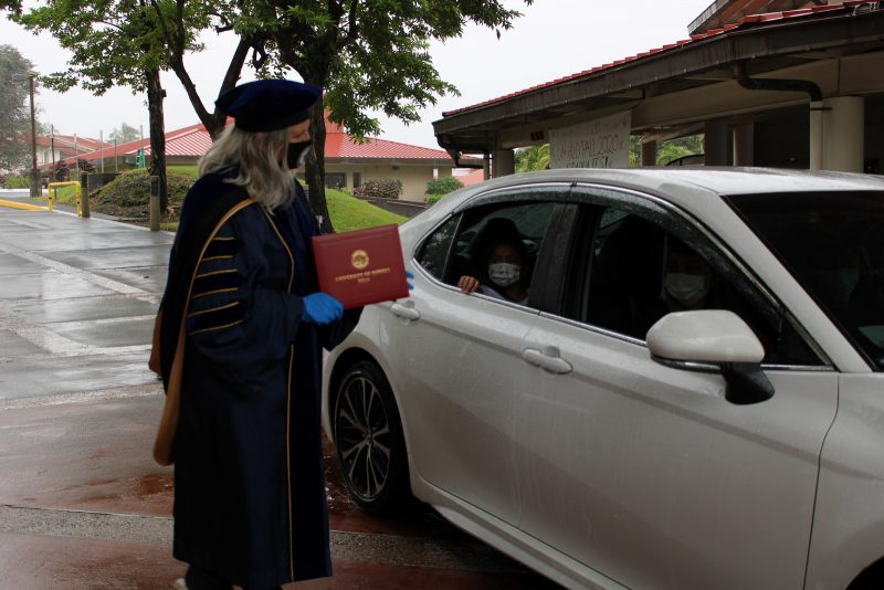 Chancellor Irwin holds diploma cover as car approaches.