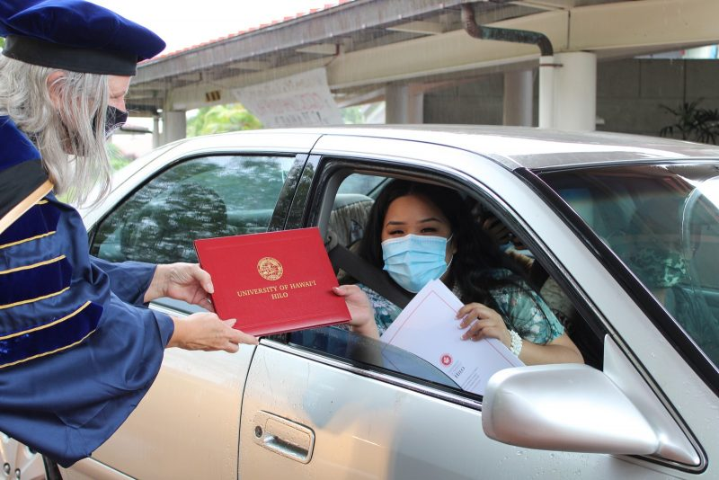 A young woman graduate in blue mask takes red diploma cover from the Chancellor.
