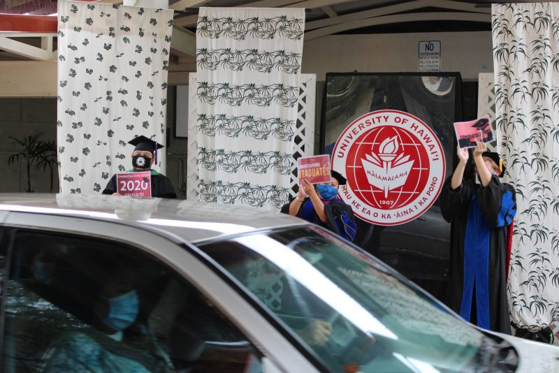 A car moves by as UH Hilo vice chancellors clap and wave to graduate.