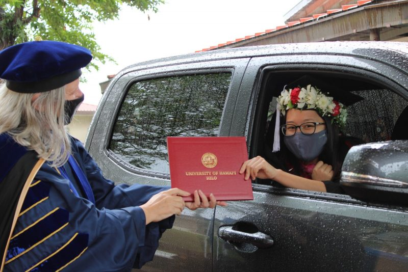 A young woman graduate in head lei takes red diploma cover from Chancellor through the rolled down car window.