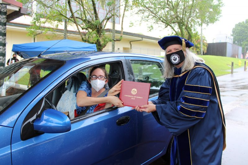 A graduate, who is driving the car, takes red diploma cover from the Chancellor through the driver's side window.