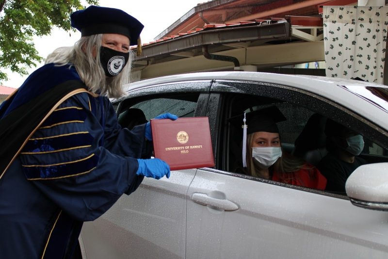 Chancellor Irwin in cap holds diploma cover so viewer can see seal. Graduate is in car with mask on.