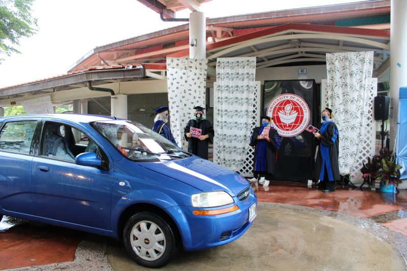 A blue car moves away after graduate receives diploma, VIPs clap and cheer.