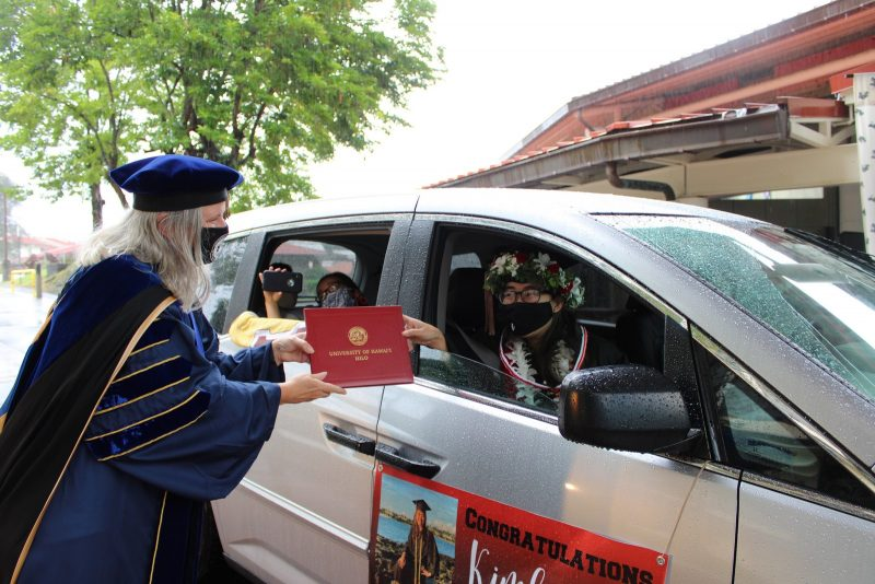 A grauate in a car with a sign on the side reaches out to take the red diploma cover from the Chancellor.