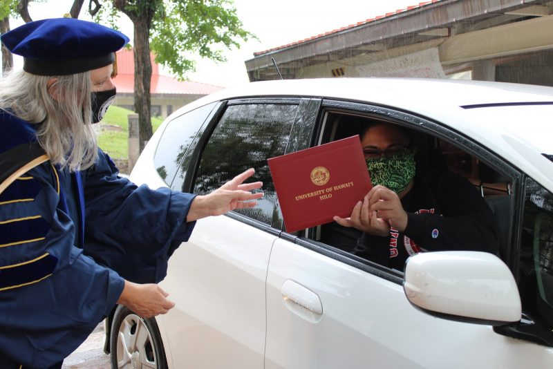 Chancello Irwin hands off diploma cover to graduate through rolled down window of car.