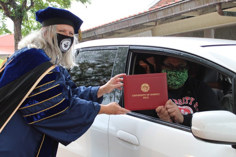 Chancellor Irwin, wearing mask and full regalia, hands red diploma cover to graduate.