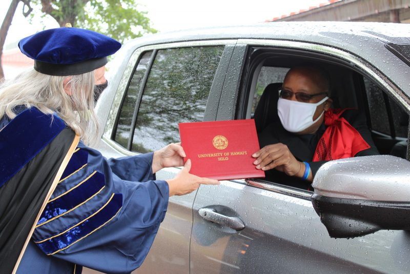 Graduate in car with white mask takes diploma from Chancellor Irwin.