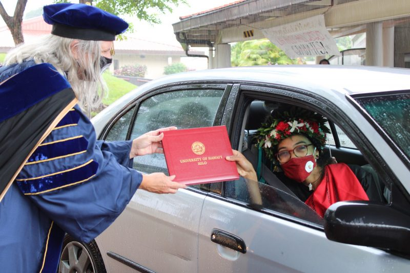 A young woman graduate in head lei and wearing a red mask, takes red diploma cover from Chancellor Irwin.