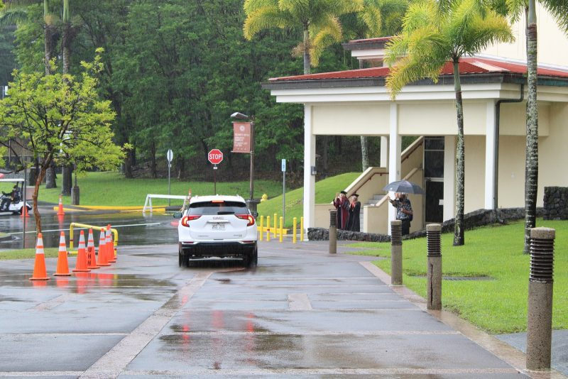 A car drives off to the campus exit after after has received diploma cover.