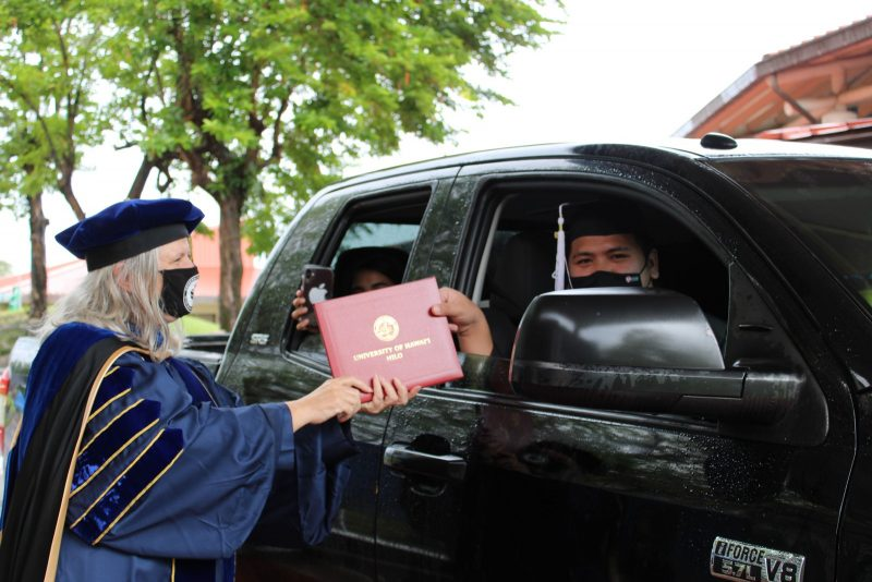 Graduate in Black truck reaches out to take red diploma cover from Chancellor Irwin.
