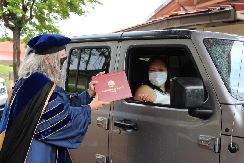 A woman graduate in white mask sits in car while Chancellor Irwin begins to pass red diploma cover through car window.