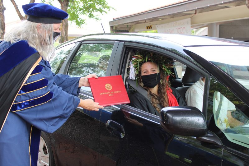 Young woman graduate in black mask sits in car as Chancellor Irwin begins to pass redd diploma cover through window.