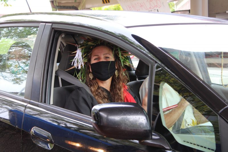 Smiling graduate in black mask sits in passenger side of vehicle.