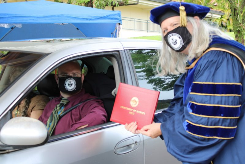 A male graduate driving car stops for Chancellor Irwin to hand him his red diploma cover. Chancellor Irwin turns her head toward camera.
