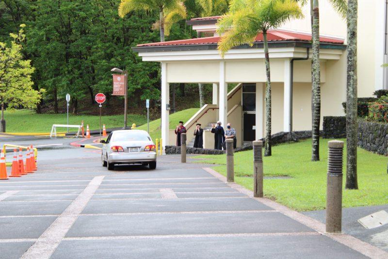 A car drives toward the campus exit.