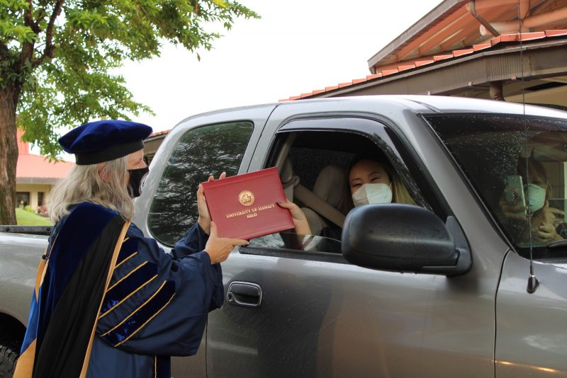 Graduate in dark gray truck wearing white mask reaches out of truck window to take red diploma cover from Chancellor Bonnie Irwin.