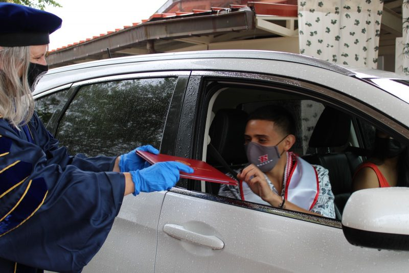 Graduate in car reaches out for red diploma cover.