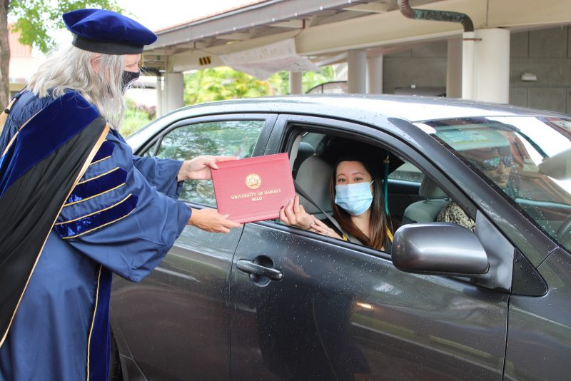 Graduate in dark gray car wearing blue mask reaches out of car window to take red diploma cover from Chancellor Bonnie Irwin.