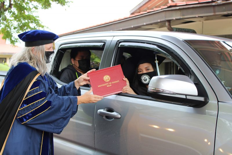 Graduate wearing black mask with white UH seal reaches out of light gray truck window to take red diploma cover from Chancellor Bonnie Irwin.