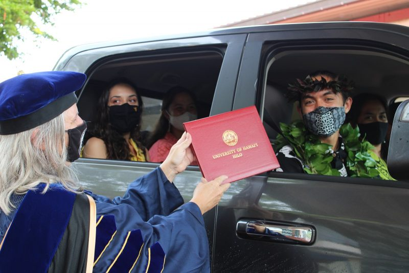 Chancellor Irwin hands red diploma cover to graduate in car full of family members.