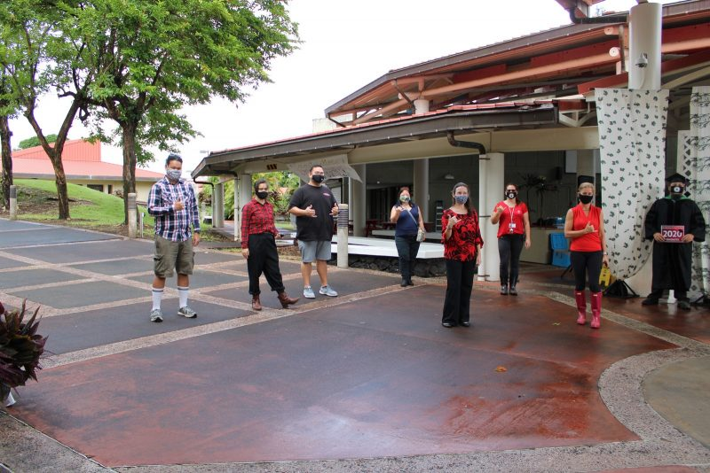A group of UH Hilo staff, most wearing red and black, who helped run the drive through event pose for a photo.