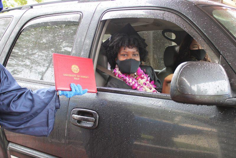 Graduate in lei and mask in car.