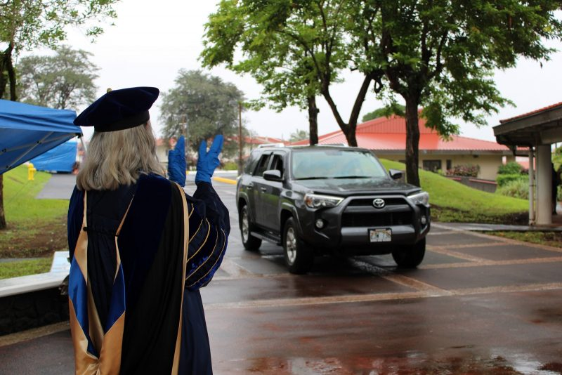 Car approaches Chancellor Irwin as she claps.