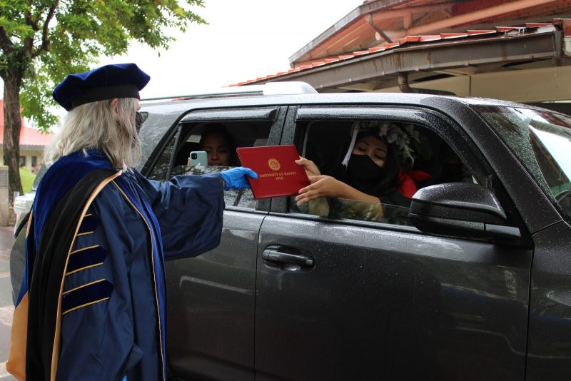 Chancellor Irwin hands red diploma cover to graduate in car.