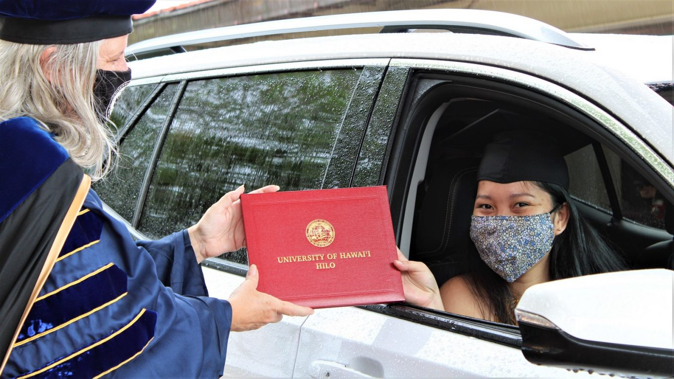 Young woman seated in passenger side of vehicle receives red UH Hilo diploma cover from Chancellor Irwin.