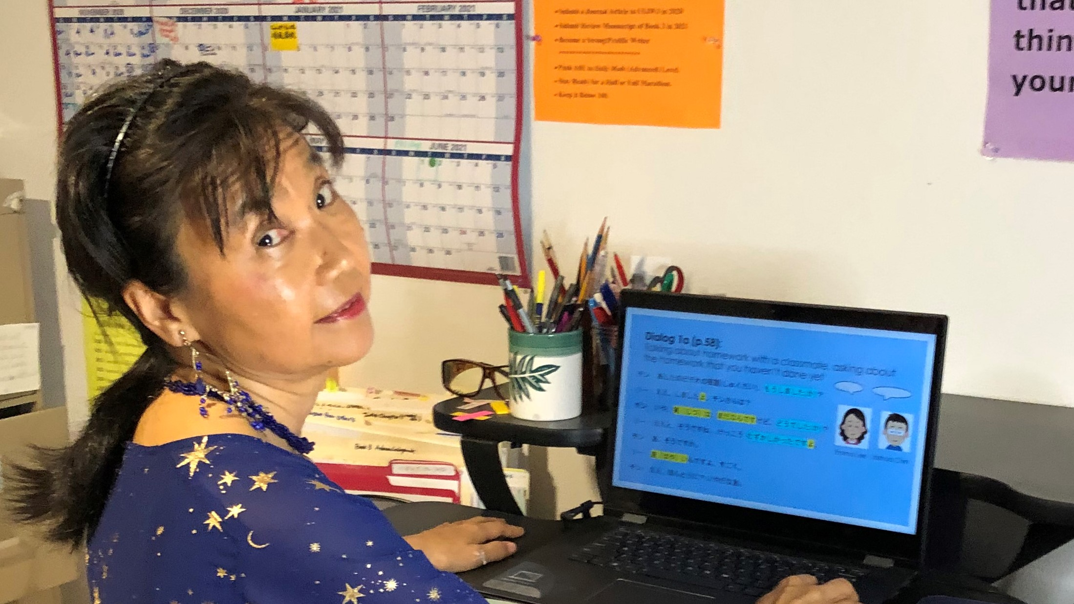 Yoshiko Okuyama in her office with a class up on the computer screen.